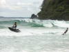 "Ricardo ""Batman"" Conte & Collin Harrington (L to R) tow into waves on a wakeboard"